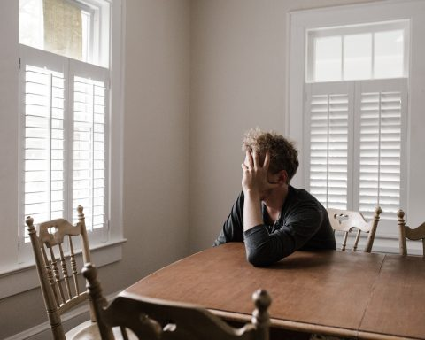 Person leaning on wood table with head resting on hand looking out a window