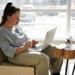 Girl wearing headphones working on laptop