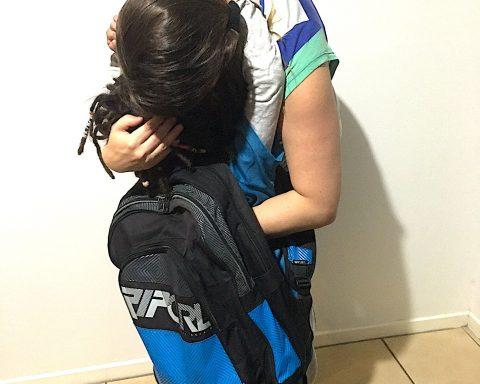 Parent or older sibling hugs child wearing backpack