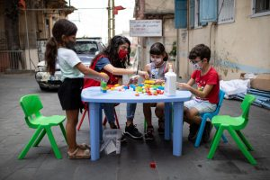 Children play with Lego on table in street wearing facemasks