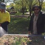 Two men water garden bed
