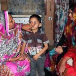 A community health worker in Pakistan providing eye care to young boy