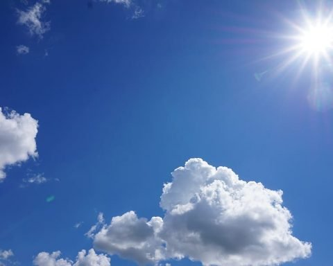 Bright blue sky with light clouds and sun in top right corner