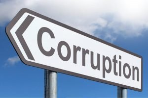 Road sign reading 'corruption' with arrow pointing left