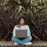 Woman sitting on wooden decking using laptop