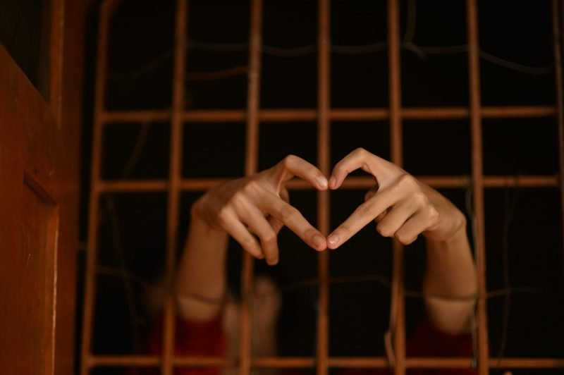 Hands reaching out of cell bars making heart gesture