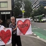 Two female protesters holding signs reading 'I welcome refugees' and 'freedom' in Melbourne CBD